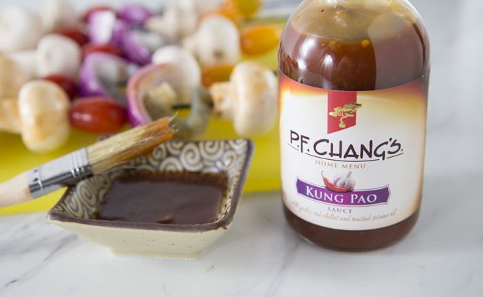 a dish of sauce with a brush and a bottle of PF Chang's Kung Pao sauce