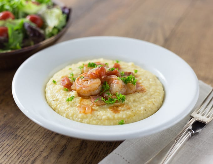 Some of the best comfort food comes from the American South and shrimp and grits ranks near the top! Shrimp and grits is true Lowcountry cuisine from coastal Carolina and Georgia. Imagine a spicy saucy shrimp with some creamy corn grits with cheese for a nice balance of flavor. This is a must try recipe and feel free to get creative. The grits are a blank canvas to add something spicy to. Like cajun flavors? Add some spicy cajun style shrimp. | ethnicspoon.com