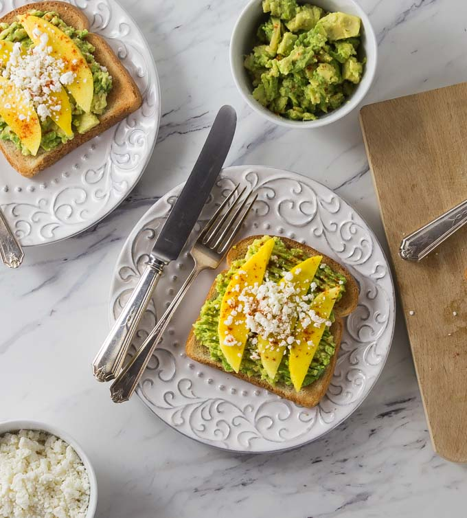 Fresh and delicious for breakfast or lunch! Try a new avocado toast recipe with Latin flair! Creamy avocados with tangy mango, salty queso fresco and a sprinkle of chili powder. The combination of flavors is incredible! | ethnicspoon.com