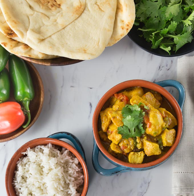 bowls of naan, cilantro, chicken xacuti, rice, and peppers