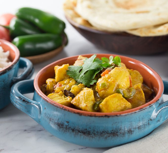 chicken xacuti in a blue bowl with naan and peppers on the back