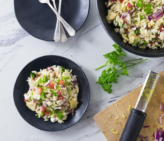Here is a super easy salad recipe to try! Take this fresh and delicious Mediterranean orzo pasta salad at your next family gathering. This is a great salad to take along to events or serve at a dinner party. This is easy and delicious salad recipe with tomatoes, feta cheese, Kalamata olives, and artichoke hearts among other things. | ethnicspoon.com