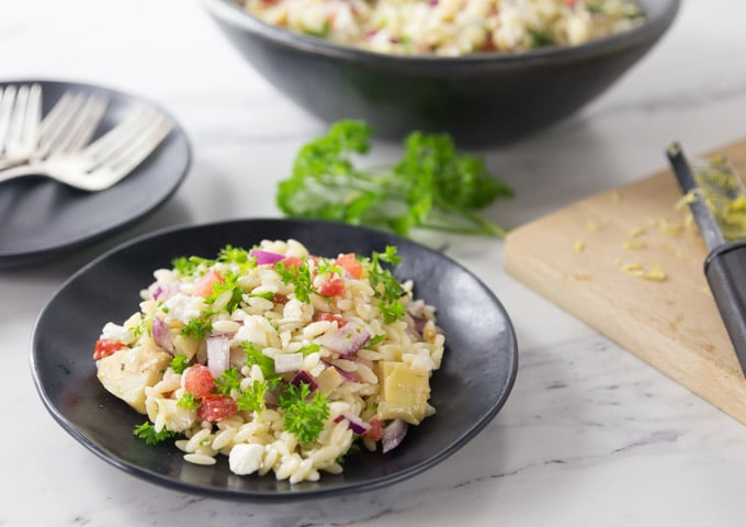 Love pasta salads? You will love this super easy salad recipe. Take this fresh and delicious Mediterranean orzo pasta salad at your next family gathering. This is a great salad to take along to events or serve at a dinner party. This is easy and delicious salad recipe with tomatoes, feta cheese, Kalamata olives, and artichoke hearts among other things. | ethnicspoon.com