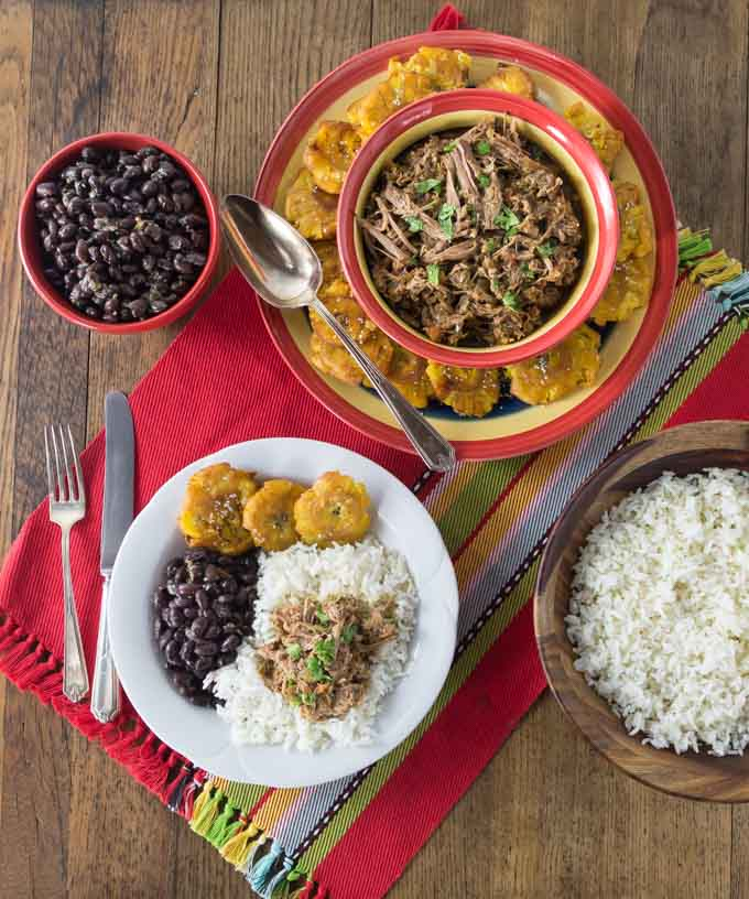 a top down view of a table with ropa vieja, plantains, beans, and rice on a red placemat