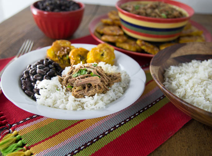 a plate of rice with ropa vieja, beans, and fried plantains with serving dishes in the back