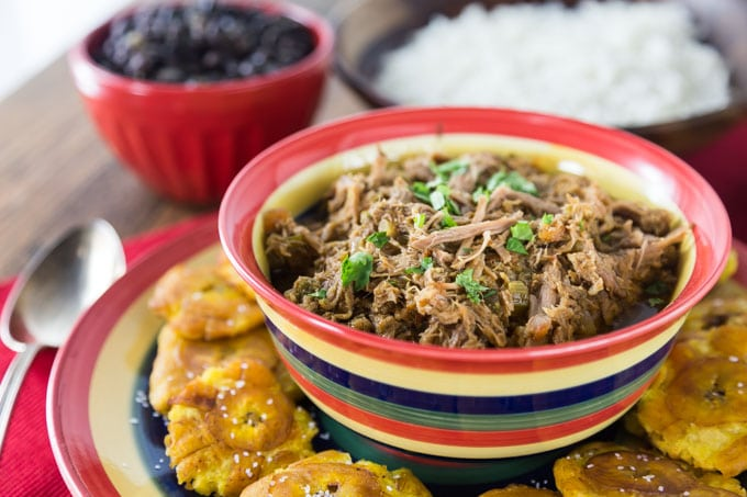 a closeup of ropa vieja on a plate with fried plantains on a saucer