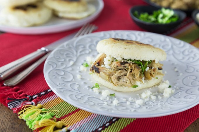 Arepas are a popular dish in Colombia and Venezuela. These are also gluten free made with corn flour or masarepa. I like to fill mine with some spicy shredded chicken and queso fresco. Here is an easy recipe to make arepas at home and the dough comes together quickly and you can brown them on a cast iron skillet or griddle. | ethnicspoon.com