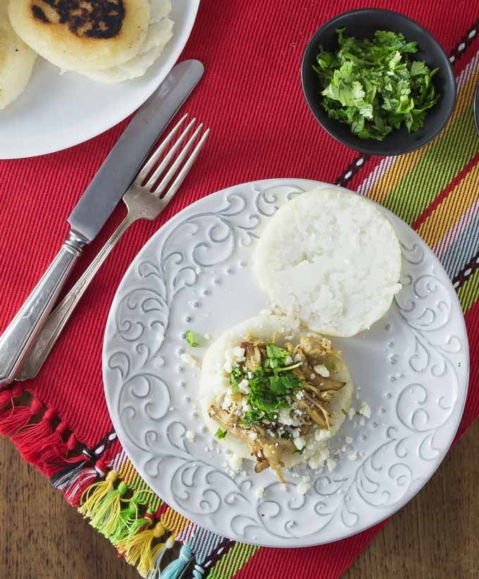 Break out the griddle and try some of these South American arepas! You'll love these nice warm arepas with a crunchy exterior and soft creamy middle. Arepas are a popular dish in Colombia and Venezuela. These are also gluten free made with corn flour or masarepa. I like to fill mine with some spicy shredded chicken and queso fresco. Here is an easy recipe to make arepas at home and the dough comes together quickly and you can brown them on a cast iron skillet or griddle. | ethnicspoon.com