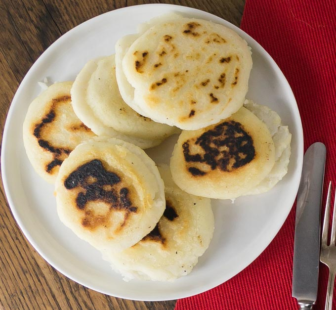 Don't be intimidated by rolling out some masa dough and frying these on a griddle. You'll love these nice warm arepas with a crunchy exterior and soft creamy middle. Arepas are a popular dish in Colombia and Venezuela. These are also gluten free made with corn flour or masarepa. I like to fill mine with some spicy shredded chicken and queso fresco. Here is an easy recipe to make arepas at home and the dough comes together quickly and you can brown them on a cast iron skillet or griddle. | ethnicspoon.com