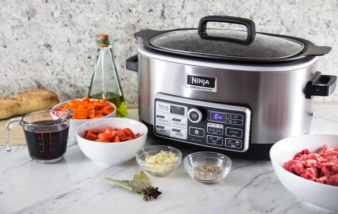 a ninja cooker on a counter with Vietnamese beef stew ingredients prepared in bowls
