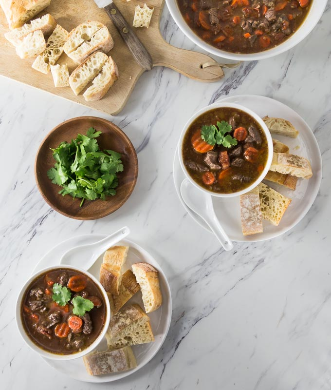 two plates of vietnamese beef stew with cut up baguette
