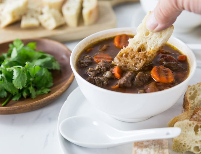 bread dipping into a bowl of Vietnamese beef stew with a plate of cilantro on the left