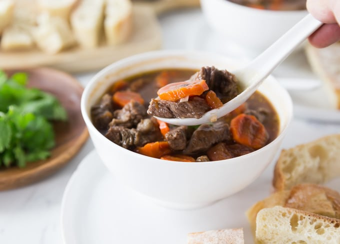 a bowl of Vietnamese beef stew on a spoon with baguette in the back