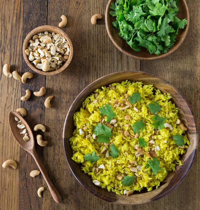 Indonesian turmeric rice in a big bowl and a bowl of cilantro and smashed cashews on the top with a spoon