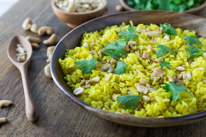 a closeup of Indonesian coconut rice with cilantro and a spoon and cashews on the left