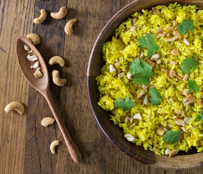 Your rice does not have to be boring! How about an exotic rice dish from Indonesia. Indonesian turmeric rice (nasi kunci) with coconut milk and cashews has such delicate flavors you will be amazed how delicious this humble dish is. You can also garnish with cilantro, coconut flakes, and crispy fried onions. #indonesianfood #nasikunci #turmeric #healthyrecipe # turmericrice | ethnicspoon.com