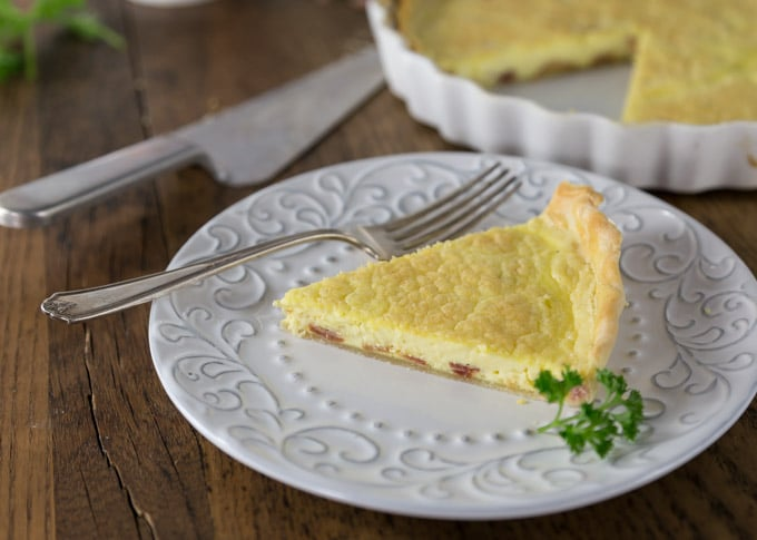Quiche Lorraine is from the North East region of France which borders, Belgium, Germany and Luxembourg. This is a dish for all meals: breakfast, brunch, lunch or dinner. This has such a rich custard like texture with a salty cheese and bacon flavors what is not to love! Simple ingredients of eggs, bacon, cream and cheese that come together in a crispy crust. Quiche Lorraine is a slice of goodness and you will love the flavor! | ethnicspoon.com