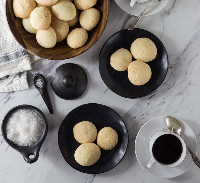 two black plates of cheese bread with a big bowl of cheese bread, salt, and coffee