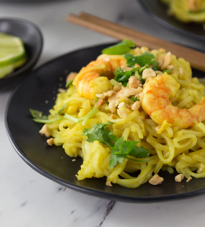 a black plate with Indonesian curry noodles with shrimp and a pair of chopsticks