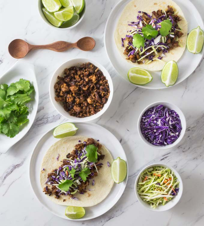 tacos on plates with lime wedges and bowls of taco meat and taco toppings