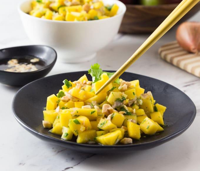 chopsticks grabbing a piece of mango salad