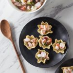 shrimp ceviche in chip bowls on black plate with wooden spoon