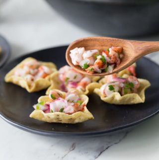 shrimp ceviche on wooden spoon with black plate and chips