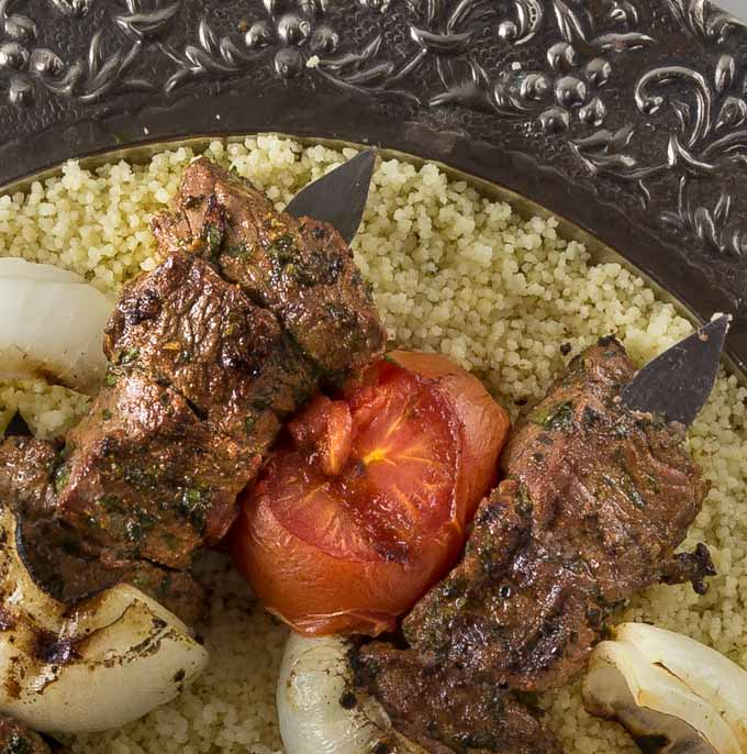 Beef kebabs on Arabic style skewers grilled with tomato, onions on a bed of couscous.