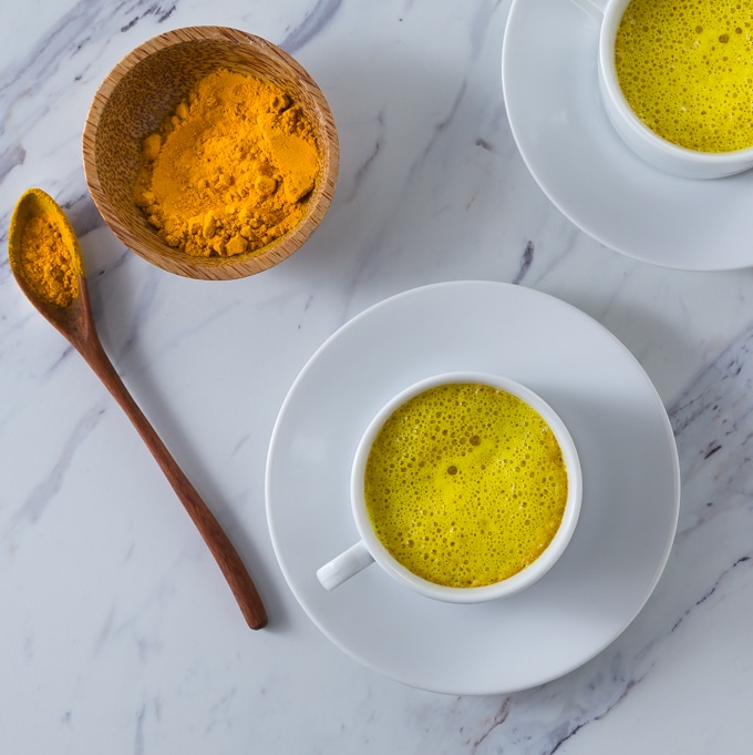 A photo of two white cups with turmeric and turmeric latte.