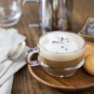 A photo of a clear coffee cup with lavender latte and some cookies.