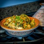 A tagine base with chicken on a stove top.